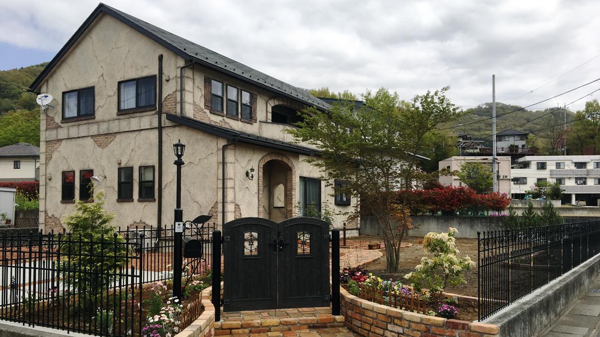 エイジングの外壁とフラワーガーデンの庭がかわいい家の外観