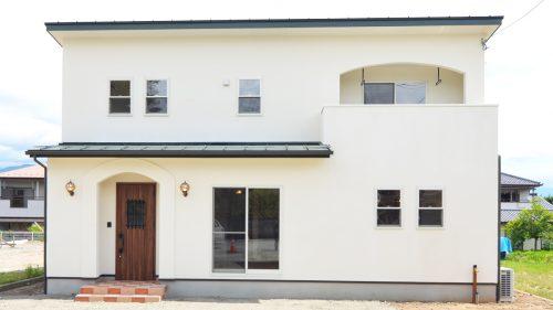 漆喰塗りの外壁にグリーンの屋根