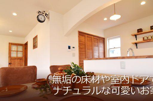 漆喰塗り壁にレンガの玄関アーチが可愛い家